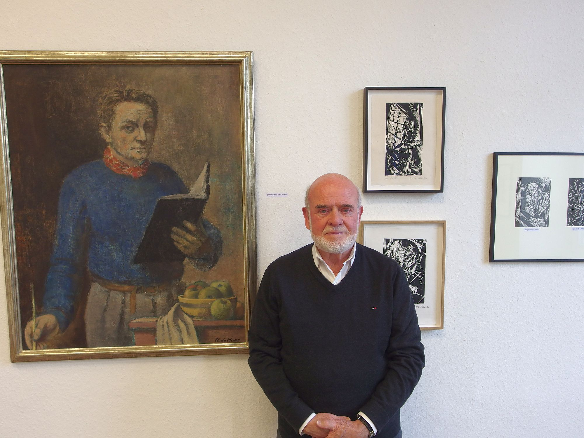 Museumsleiter und Vorsitzender des Heimat- und Bürgervereins Kaiserswerth e.V. Wilhelm Mayer vor einen Selbstportrait und Druckgrafiken von Adolf de Haer. Foto: SO